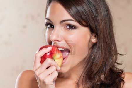 Photo for Portrait of pretty young woman eating an apple - Royalty Free Image