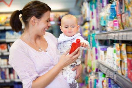 Foto de Alegre madre jugando con bebé y pasar tiempo en la tienda de compras - Imagen libre de derechos