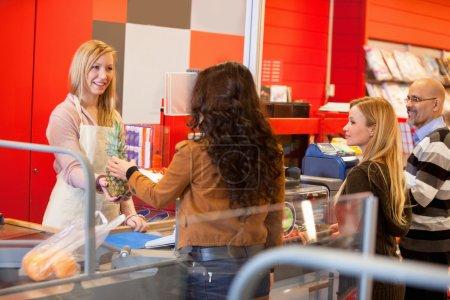 Foto de Vista de dependienta feliz con el cliente en supermercado con piña - Imagen libre de derechos