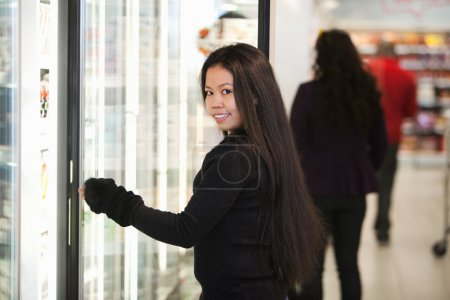 Young woman smiling while opening refrigerator in supermarket