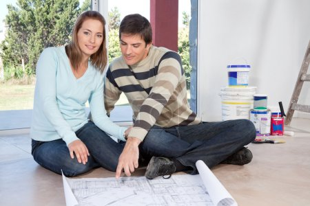 Couple sitting on the floor with blueprint of their new house