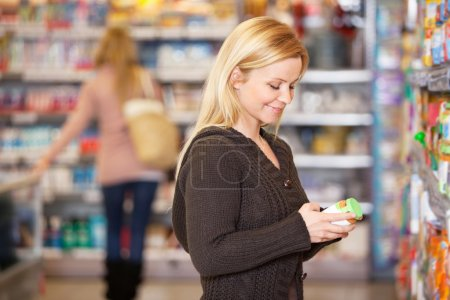 Happy young woman shopping in the supermarket