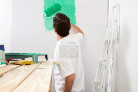 Photo for Man painting the wall with roller and brush, stepladder in background - Royalty Free Image