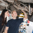 Young mechanic and woman looking at machine of car...