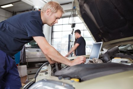 Photo for Mechanic using laptop while working on car with in background - Royalty Free Image