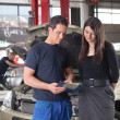 Mechanic showing the cost of service to female cli...