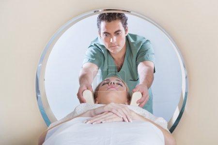 Photo pour Infirmière préparant la jeune femme au test CT scan - image libre de droit