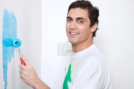 Photo pour Gros plan portrait de l'homme heureux mur de peinture avec rouleau - image libre de droit
