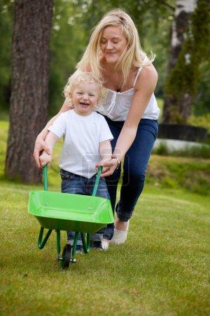 Foto de Una madre jugando con su hijo empujando una carretilla al aire libre - Imagen libre de derechos