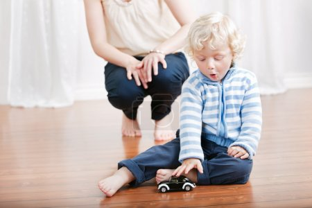 Photo for Expressive baby boy playing with a toy car with mother in the background - Royalty Free Image