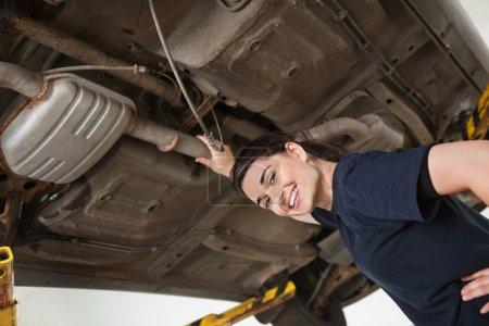 Photo pour Vue à angle bas de sourire jeune femme mécanicien réparation de voiture dans l'atelier de réparation automobile - image libre de droit