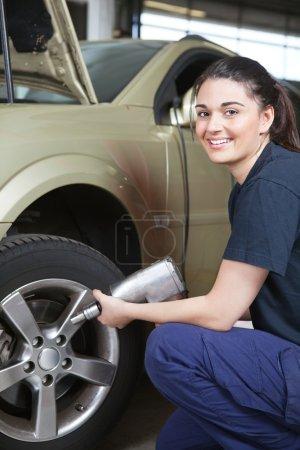 Photo pour Portrait d'un mécanicien féminin heureux changeait un pneu dans un magasin - image libre de droit