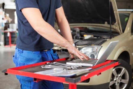Photo for Mid section of mechanic working on laptop in a garage - Royalty Free Image