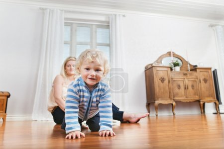Baby crawling with mother in the background
