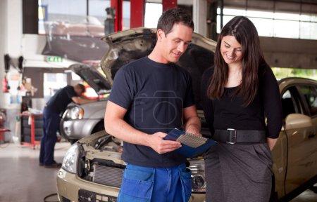 Photo pour Un client de mécanicien et femme homme discutant des réparations effectuées sur son véhicule - image libre de droit