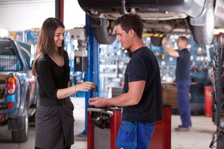 Photo pour Atelier de réparation un client heureux de livrer une voiture sur une auto - image libre de droit