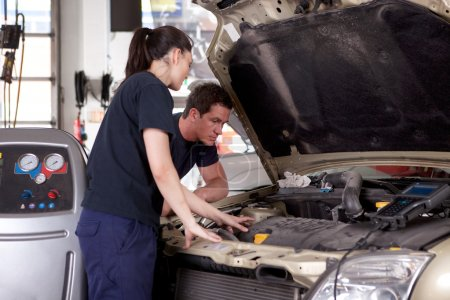 Photo for A man and woman mechanic working on a car in a auto repair shop - Royalty Free Image