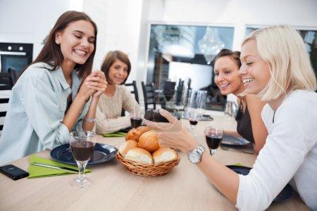 Photo pour Femmes montrant quelque chose à ses amis sur le téléphone portable à table - Profondeur peu profonde du champ accent critique sur le téléphone . - image libre de droit