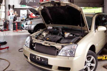Photo pour Une voiture à un atelier de réparation auto professionnel avec hotte jusqu'à - image libre de droit