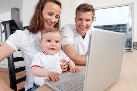 Photo pour Famille de trois personnes à l'aide d'un ordinateur portable à la maison - image libre de droit