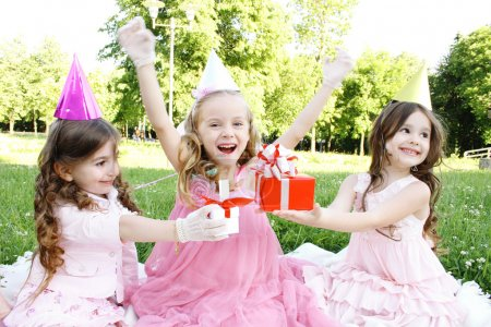 Photo for Three young girls outdoors merry, celebrate a birthday, give gifts - Royalty Free Image