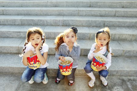 Three little girls friends eat popcorn