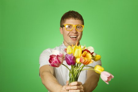Photo for Close-up of an attractive young man in shirt bow tie and glasses holding a bouquet of tulips. Nerd - Royalty Free Image
