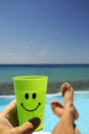 Photo for Man with a drink resting over the sea - Royalty Free Image