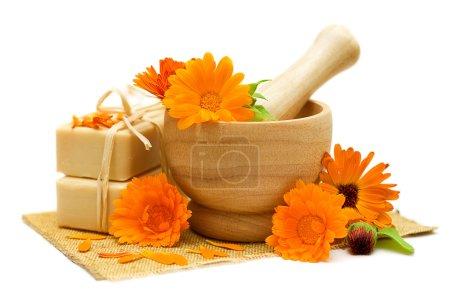 Photo pour Fleurs de calendula avec savon de bain isolé - médecine alternative et le traitement à base de plantes - image libre de droit