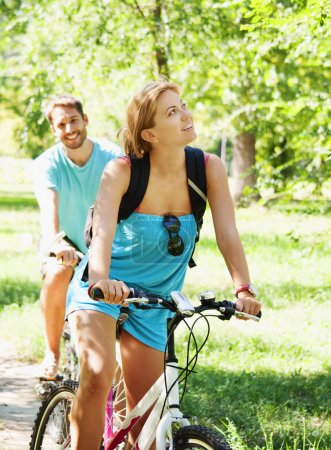 Photo for Young man and woman having a bike ride in nature - Royalty Free Image