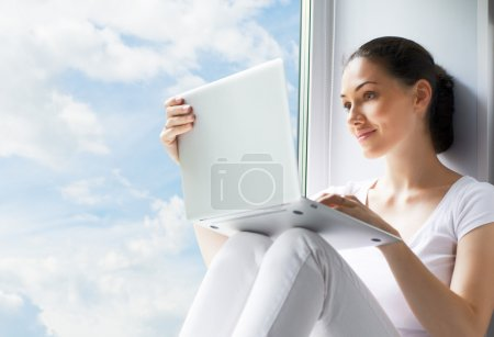 Photo for Girl working on computer in light room - Royalty Free Image