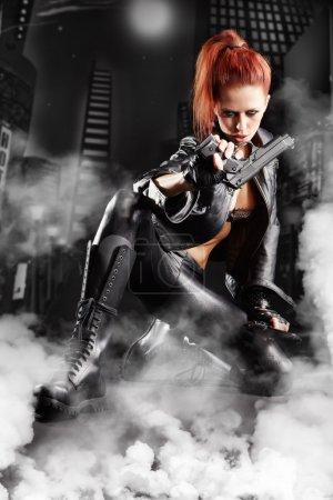 Photo pour Belle fille sexy tenant pistolet. fond de fumée - image libre de droit