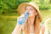 Girl in straw hat drinks water