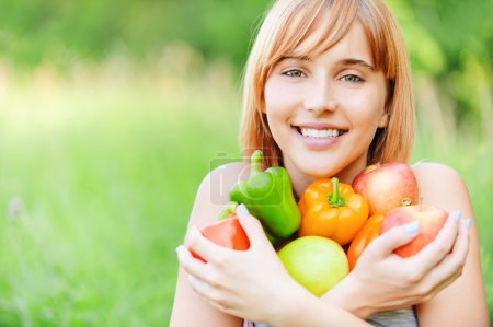 Beautiful girl with apples and sweet pepper