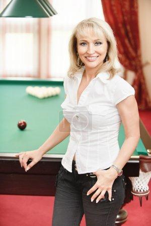 Photo pour Mature belle femme joue au billard dans la chambre . - image libre de droit