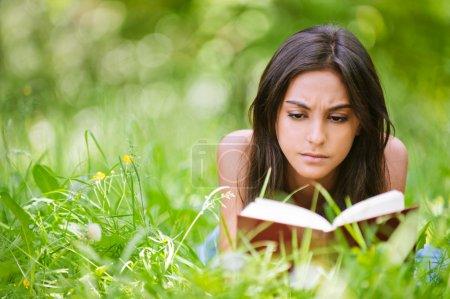Photo pour Jeune belle femme attentive se trouve sur l'herbe verte et lit livre contre parc de la ville . - image libre de droit