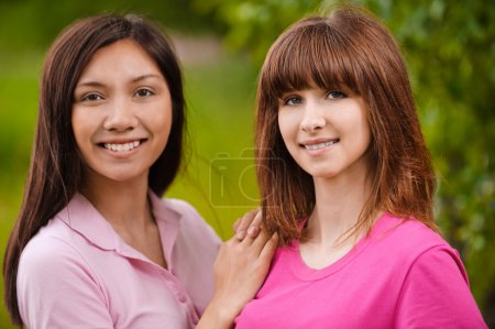 Photo for Two young smiling brunette bright clothed women standing in park. - Royalty Free Image