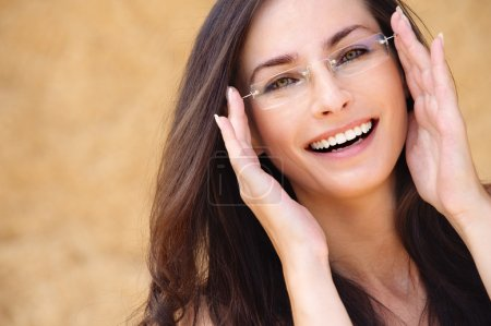 Photo for Close-up portrait of young beautiful brunette woman wearing glasses against beige background. - Royalty Free Image