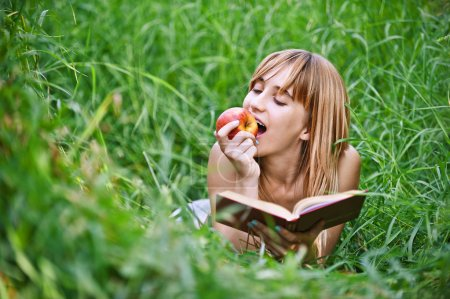 Young woman eating apple and reading book