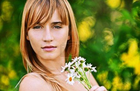 Portrait jeune femme tenant bouquet de camomilles