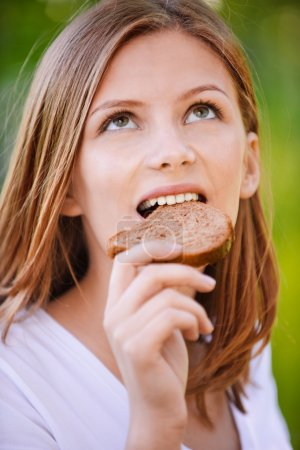 Portrait of beautiful young woman eating bread