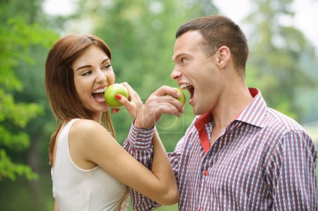 Photo for Young couple of laughing eating tasty apples at summer green park. - Royalty Free Image