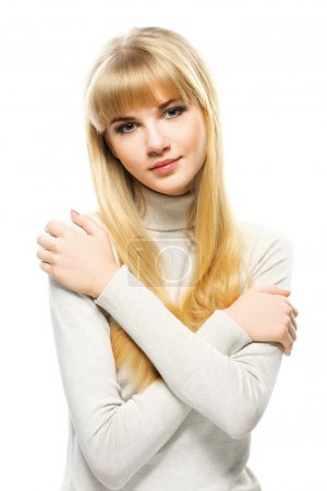 Portrait of young alluring blonde woman embracing herself