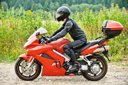 Motorcyclist driving against peaceful scenery
