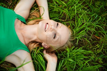 Portrait of young pretty woman lying on grass