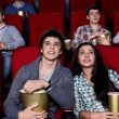 Young are closely watching a movie at the cinema...
