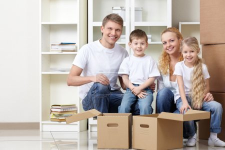 Photo for Families with kids and boxes indoors - Royalty Free Image