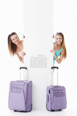 Photo for Young girls with suitcases and empty billboard on a white background - Royalty Free Image