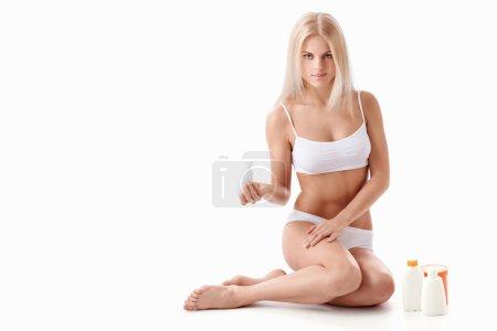 Photo pour Jeune fille avec un tube de crème sur fond blanc - image libre de droit