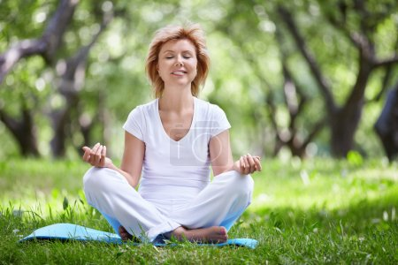 Photo for Mature woman in a park yoga - Royalty Free Image